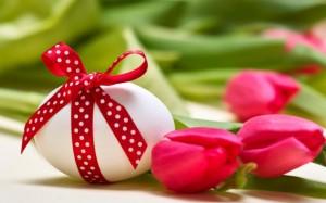 Velykų kiaušinis apjuostas raudona juostele ir raudonos tulpės